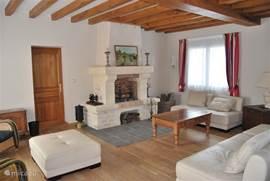 Een bijzonder sfeervolle woonkamer met schouw. Een kamer om heerlijk in te relaxen. Een echt familiehuis.