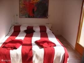 Rode kamer beneden met dubbel bed en openslaande deuren naar tuin