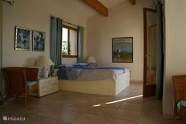 Masterbed room beneden rechts openslaande deuren naar terras, links ramen naar tuin