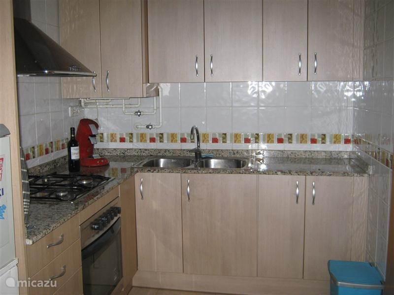 Keuken van alle gemakken voorzien voor 6 personen ingericht. Er is een doorkijk vanuit de keuken zodat u altijd contact houd met de woonkamer.