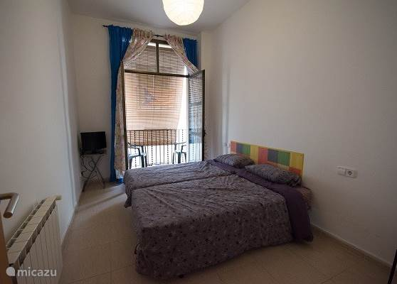 Deze twee persoons slaapkamer heeft twee eenpersoons bedden deze zijn apart opgemaakt. Er zijn twee grote openslaande deuren naar een rustiek balkon. En er staat een tv.