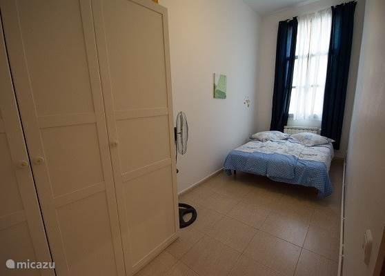 Deze langwerpige slaapkamer heeft een tweepersoonsbed en een driedeurs kast er staat in deze kamer ook een opvouwbaar kinderbedje.