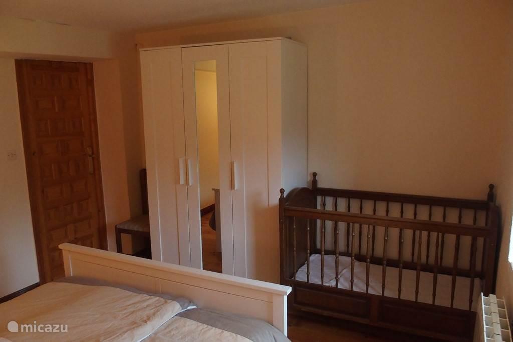 Slaapkamer 1 met een tweepersoonsbed, ledikant en kledingkast