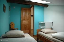 Slaapkamer 5 met twee éénpersoonsbedden en een ladekast.