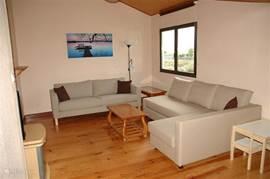 Woonkamer met ruime hoek/slaapbank, 3 zits bank, televisie en zicht op de tuin.