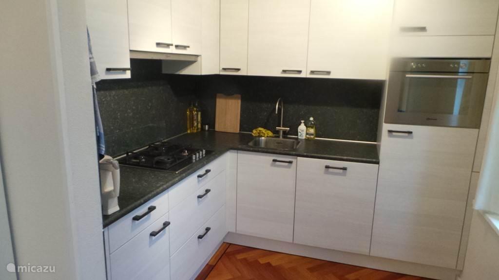 Moderne keuken (2014) voorzien van vaatwasser, oven, koelkast met vriesvak en gasfornuis