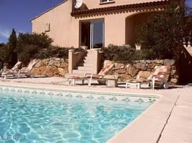 De achterkant van de villa met het zwembad.