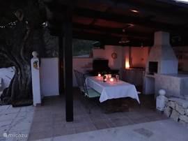Buitenkeuken en eettafel om 's avond buiten te dineren en te genieten van een glas wijn.