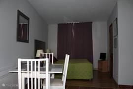 Doorsnede in de lengterichting naar de achterzijde, met op de voorgrond de eettafel met Franse stoeltjes, daarachter het 2 pers. bed en rechts de TV en de deur naar de badkamer.