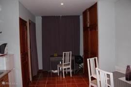 Lengte doorsnede van dit appartement richting entree. Voor de openslaande ramen staat een stoel met bureautje.
