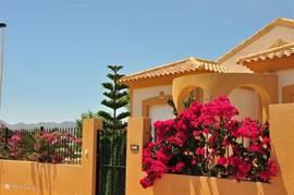 Het (schuin) vooraanzicht van villa Antojo met op de achtergrond het uitzicht dat te zien is van uit de villa.