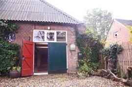 Achterkant van de boerderij met eigen ingang voor gasten en parkeergelegenheid.