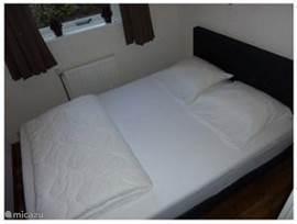 De ouderslaapkamer, is voorzien van een 2-persoons-boxspring (140 x 200), kussens en lits-jumeaux dekbed. Er staat tevens een klein kastje met 3 lades.