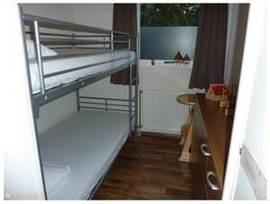 Slaapkamer met een stapelbed, voorzien van moltons, kussens en éénpersoons dekbedden. Tevens staat er een kinderstoel en is er de nodige kastruimte.