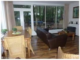 Gezellige woonkamer met sfeervolle houtkachel, openslaande tuindeuren en uitzicht op de (bos)tuin en de speeltoestellen.