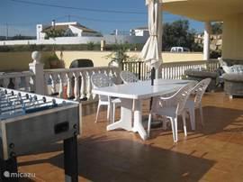 Het grote terras vormt de verbinding tussen de woonkamer/keuken en het zwembad.