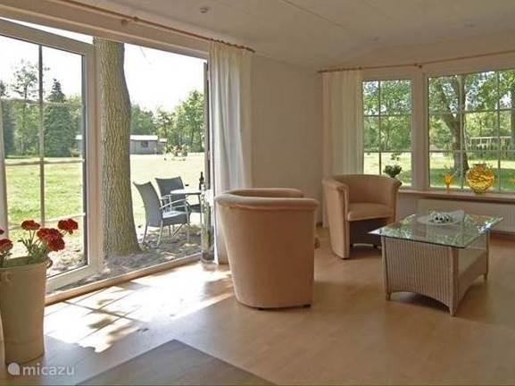 De woonkamer heeft een laminaat vloer en een prachtig uitzicht door de grote ramen, en is uitgerust met bank en luxe stoelen.