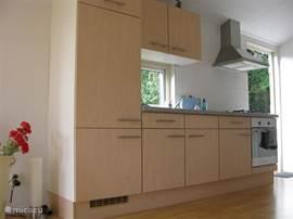 De moderne keuken is voorzien van een keramische kookplaat en afzuigkap, verder staat er een magnetron, koelkast en kleine diepvries ter beschikking.