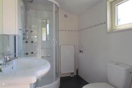 De badkamer heeft een prettige douchecabine en de wastafel heeft kastruimte voor meerdere personen.