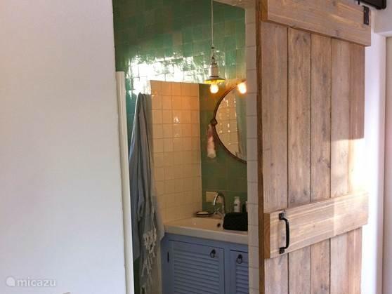 De grote houten staldeur met daarachter de badkamer met dubbele wastafel, inloop (stort)douche, toilet en origineel tegelwerk (Marokkaanse Zeliges)