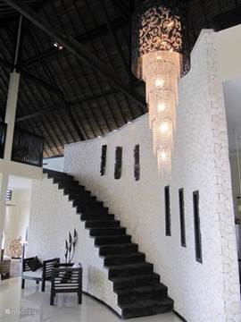 inkomhal en trap naar lounge ruimte met poolbiljard