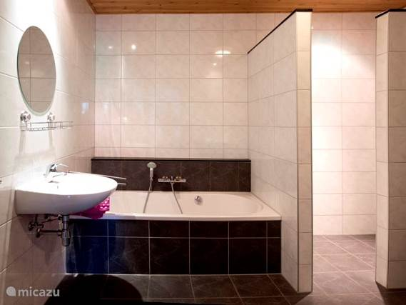 Grote badkamer op de eerste verdieping met ligbad, 2 wastafels, toilet en grote inloopdouche. De vloertegels zijn heerlijk verwarmd met vloerverwarming.
