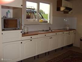keuken met keukenraam met zicht op de achtertuin.