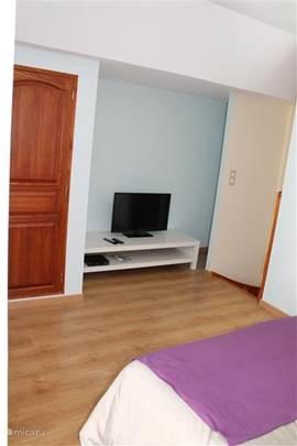 Op de slaapkamer flatscreen TV, welke is aangesloten op de kabel. Links bevindt zich de deur van de ruime inbouwkast
