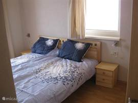Tweepersoons slaapkamer met balkon en lcd televisie met dvd speler