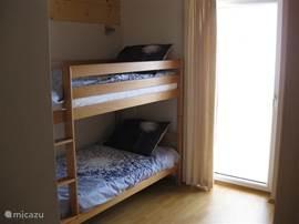 Slaapkamer met stapelbed, balkon en lcd televisie met dvd speler