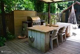 Overdekt terras naast het huis bij de tuindeuren, voorzien van een royale steigerhouten tafel met zes stoelen en een buitenkeuken.