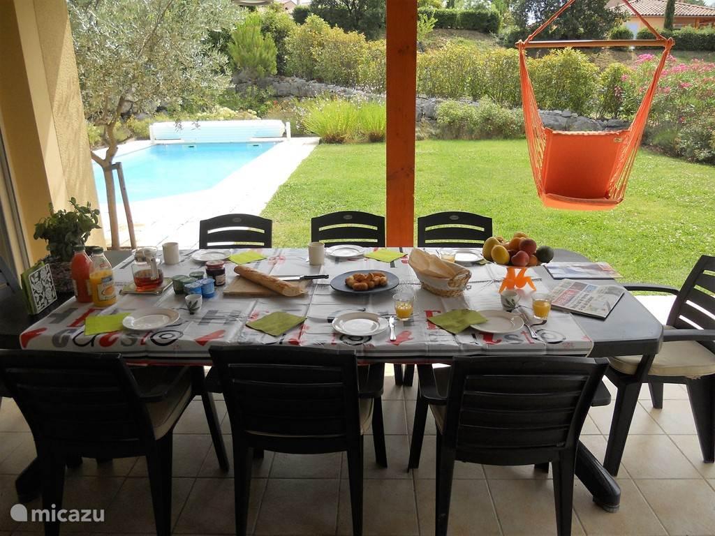 gezellige ontbijttafel met mooi zicht op tuin en zwembad