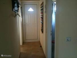 Vanuit de hal gaat men links naar de slaapkamer en rechts naar de badkamer.
