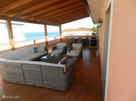 the beautiful terrace with a beautiful lounge set and BBQ and large table with 8 chairs