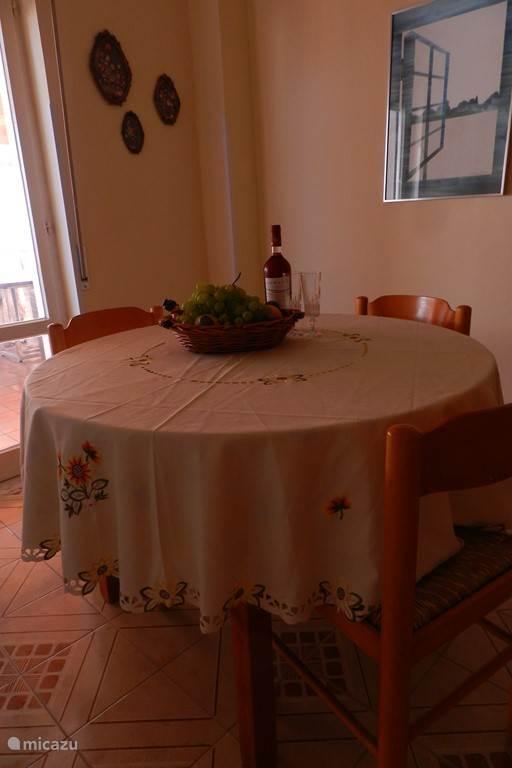 entree met tafel en 4 stoelen met openslaande deuren naar het terras