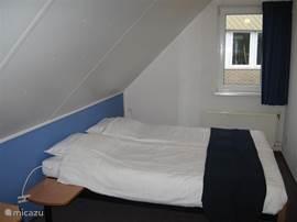 Slaapkamer 2. Met openslaande raampartij. 2 bedden met lattenbodems 80x200. Ruime hang/legkast
