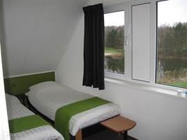 Slaapkamer 3. Met openslaande raampartij. 2 bedden met lattenbodems 80x200 Ruime hang/legkast.