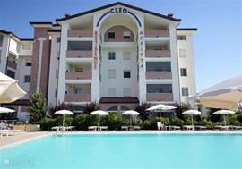 Residence met zwembad en ruim zonneterras voorzien van parasols en ligbedden.