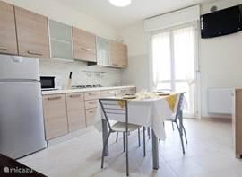 Woon/eetgedeelte met ruime keuken voorzien van alle gemakken, eettafel en stoelen, eenpersoonsslaapbank en satelliet TV met voorgeprogrammeerde zenders.
