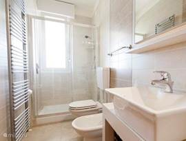 Bathroom with shower, toilet, bidet and washbasin.