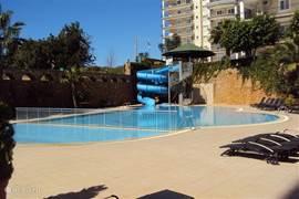 Zwembad met glijbaan en kinderbad.