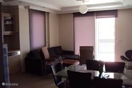 Woonkamer met deur tot balkon. In deze foto ziet u de stoelen van het balkon in de woonkamer.