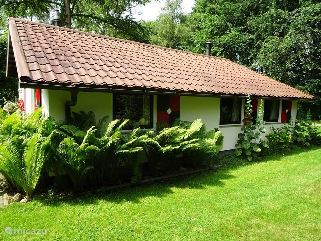 Aan de  achterzijde van de bungalow bevinden zich de slaapkamers met openslaande ramen met ten dele voorzien van horren.