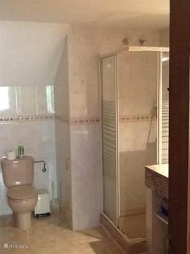 Badkamer begane grond met douche en toilet met directe toegang naar de slaapkamer en de woonkamer