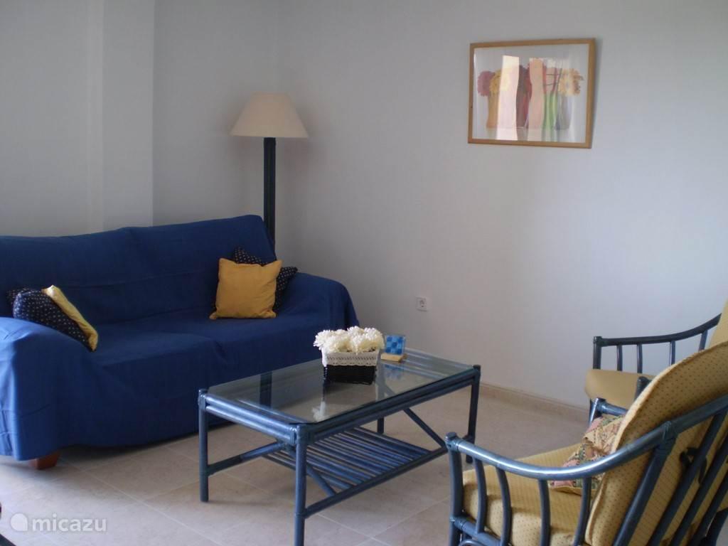 De zithoek van de woonkamer met salontafel, lectuurbak en gastenboek voor tips van de vorige gasten.