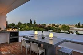 Terras boven met kleine buitenkook faciliteiten / grilplaat, eettafel en zitbank.