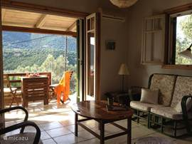 De woonkamer in het gastenverblijf met openslaande deuren naar het terras.
