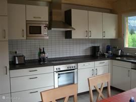 De ruime keuken met alles erop en eraan.