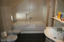 De mooie badkamer op de eerste verdieping met bubbelbad, toilet, bidet, wastafel en toegang tot de sauna.
