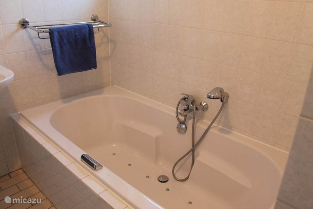 Whirlpool op de begaande grond , deze badkamer heeft ook nog een douche.